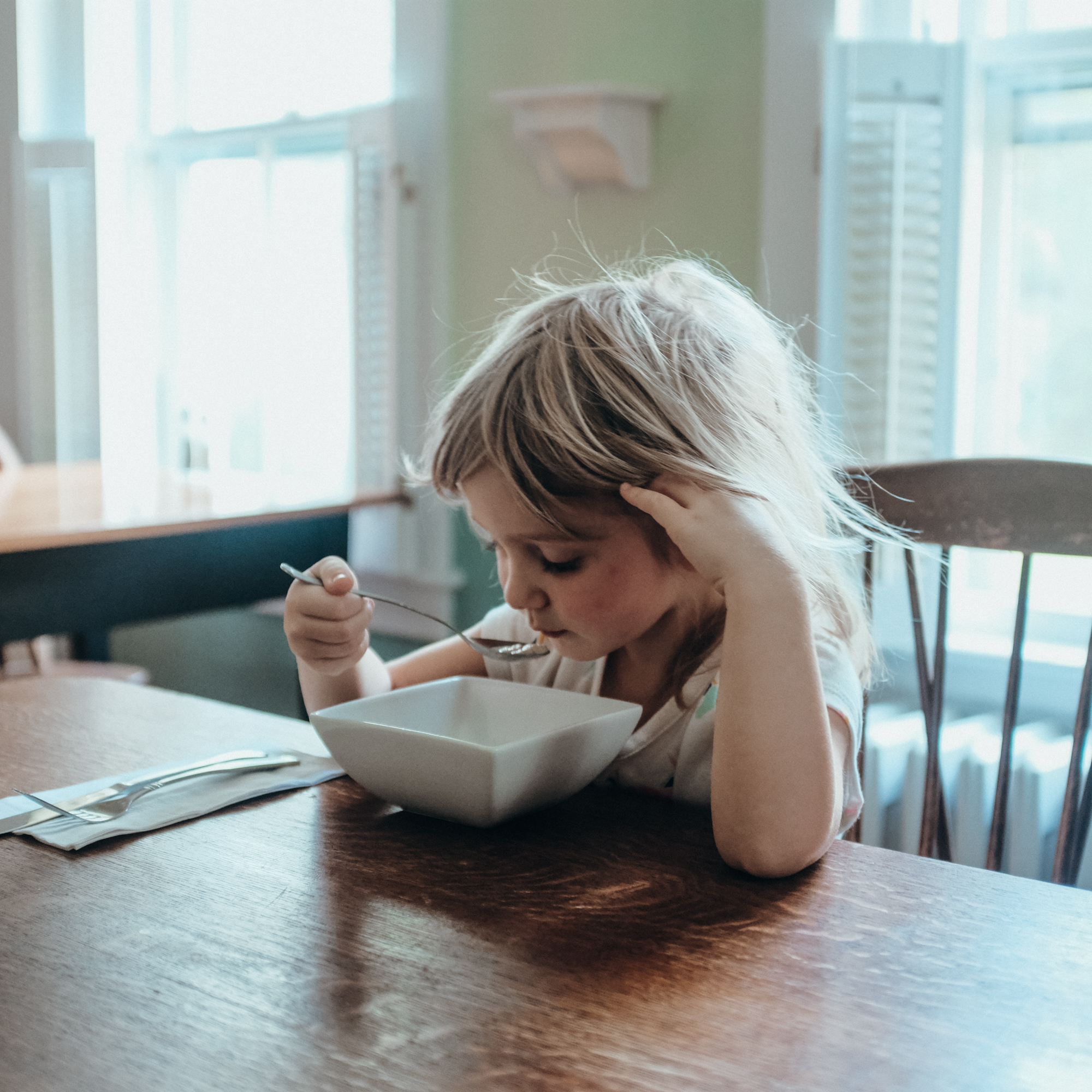 A girl eats a bowl of cereal at a wooden table, New Hampshire.
