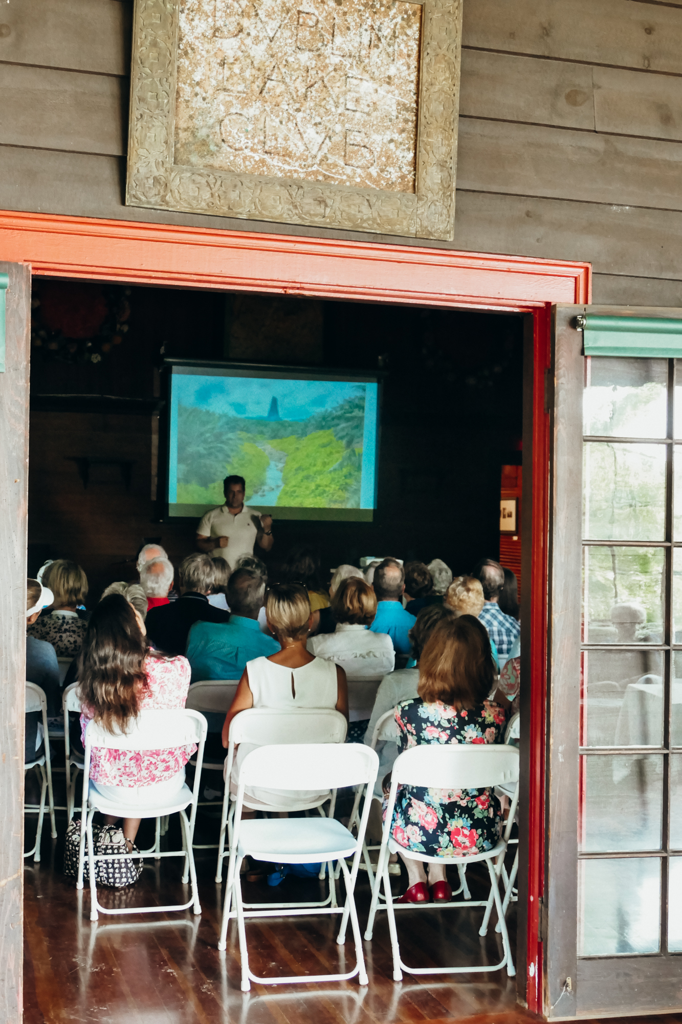 A photographer gives a talk in front of an audience in a wooden building in Dublin, New Hampshire.