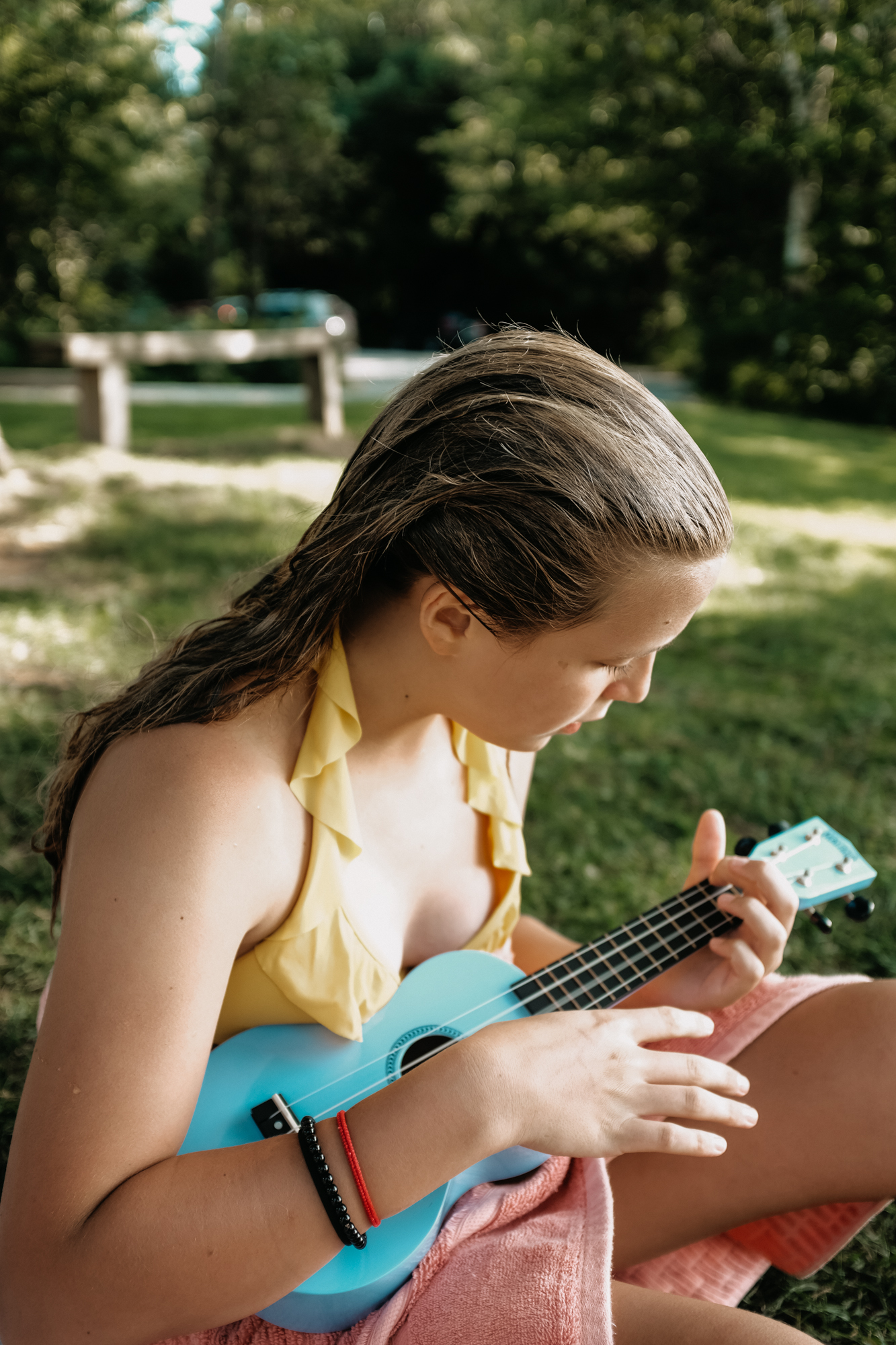 A blond girl plays a blue ukulele in a bathing suit.