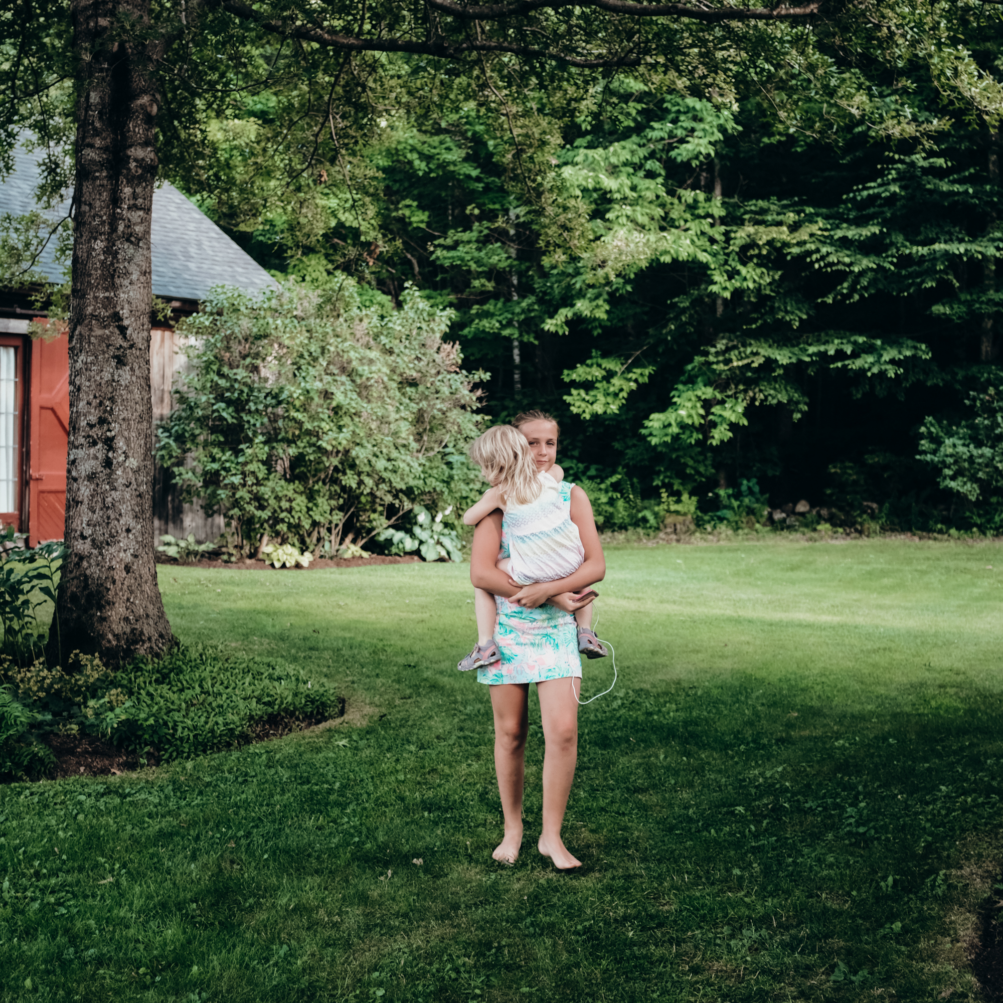 A girl carries a younger girl across a lawn in summer in New Hampshire.