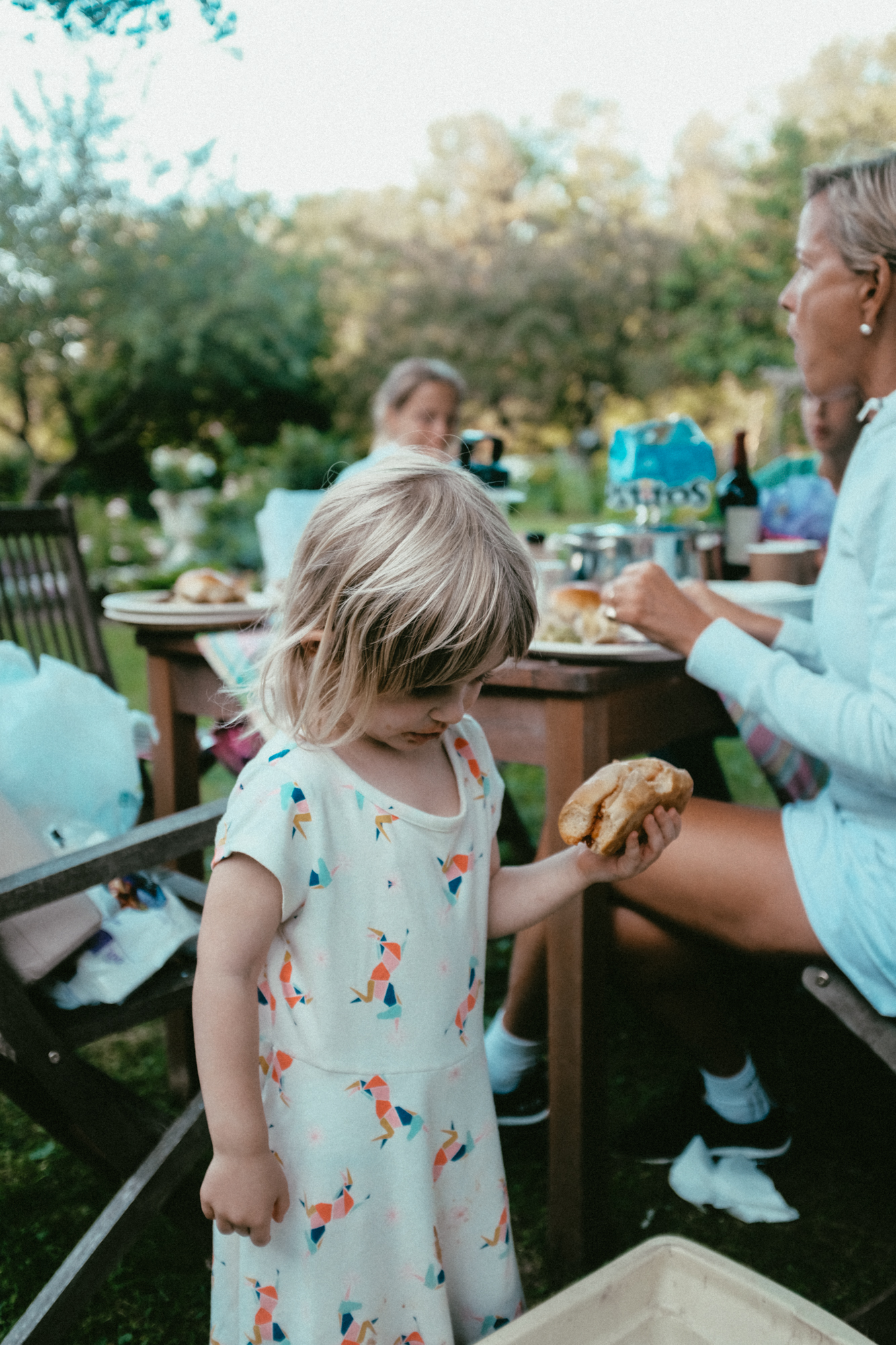 A little girl looks is surrounded by people at a barbeque