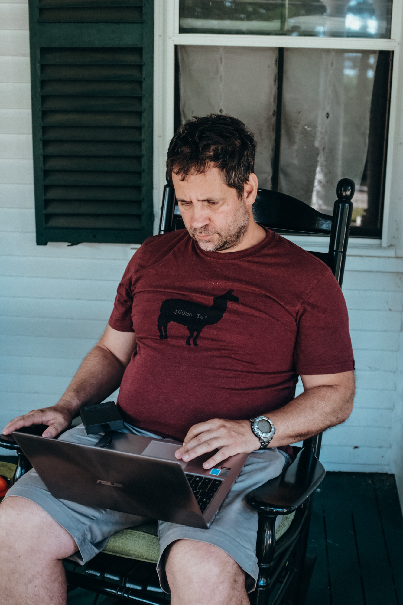 A man works on his computer in a rocking chair on a front porch in Jaffrey, New Hampshire.