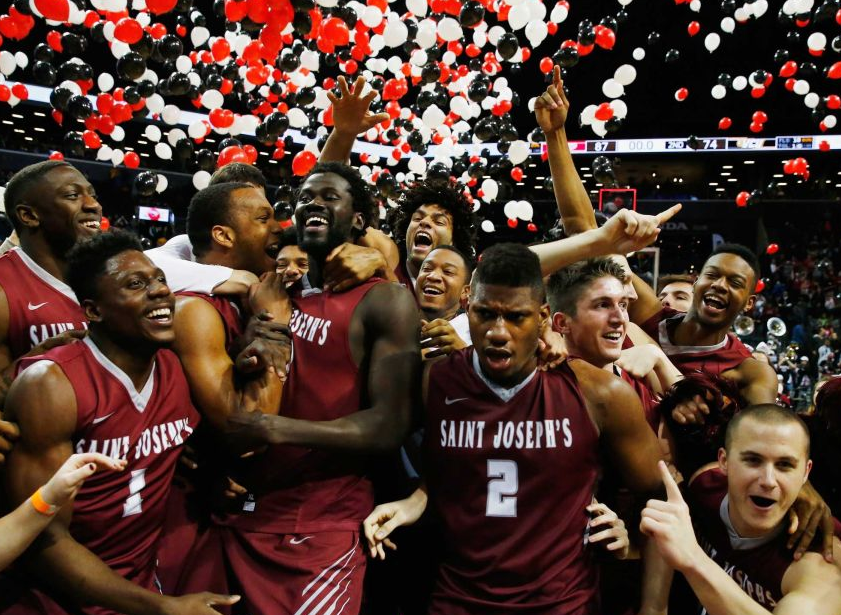 Papi Ndao celebrates with St. Joe's teammates after beating VCU in the A-10 Championship