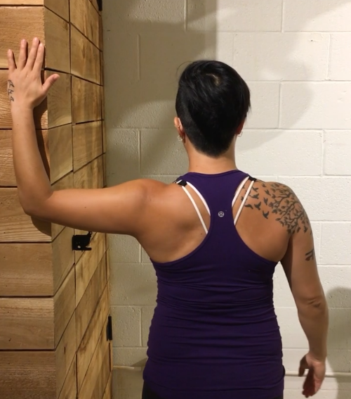 Janna Young holistic life coach and Pilates instructor demonstrating the chest stretch. Photo courtesy of Janna Young of Seek to Find.