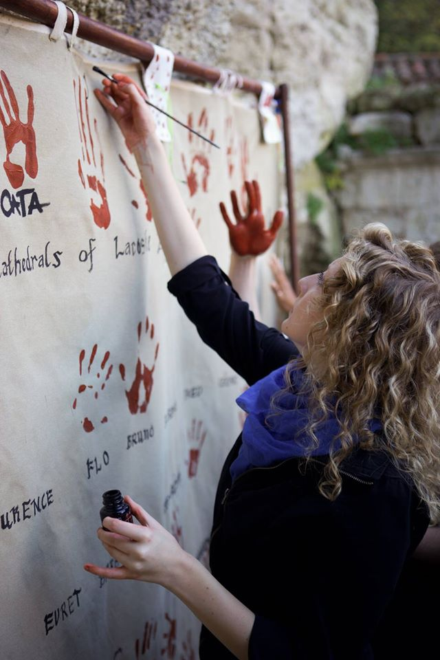 Hannah Breshears signs her name after making a handprint- a signature method chosen by Rex Hausmann because of its origins in ancient artwork.