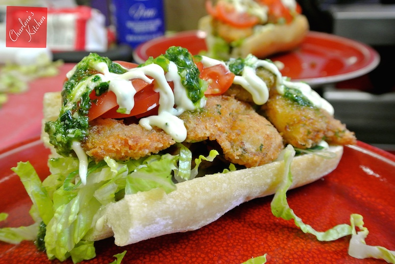 Po'boy with breaded shrimp on a ciabatta roll with lettuce, garlic aioli, spinach pesto, and tomato. Just looking at this picture made us crave these shrimp po'boys again!