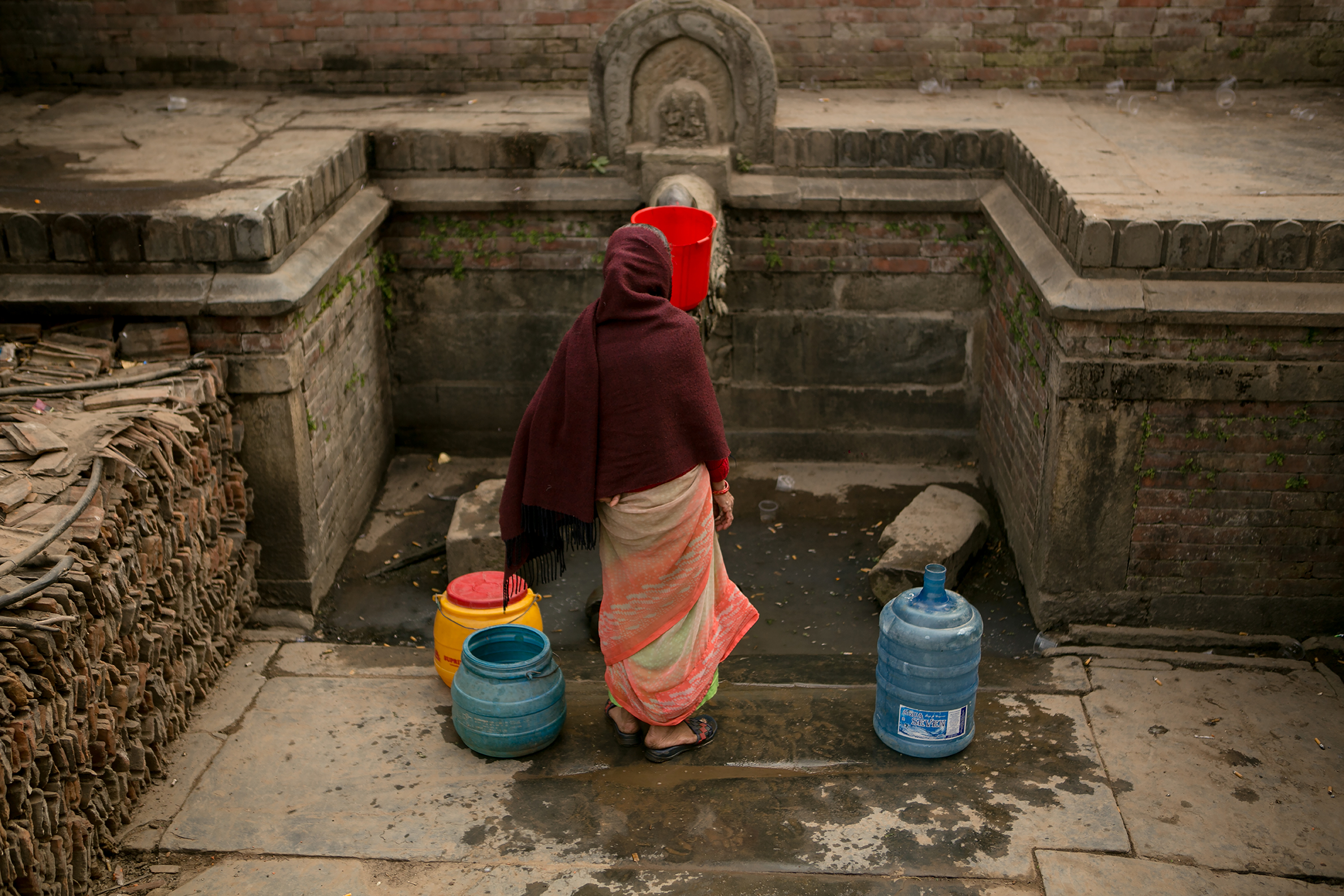 BHAKTAPUR, NEPAL — A woman stands still in front of a public well as she waits for water to fill her containers.
