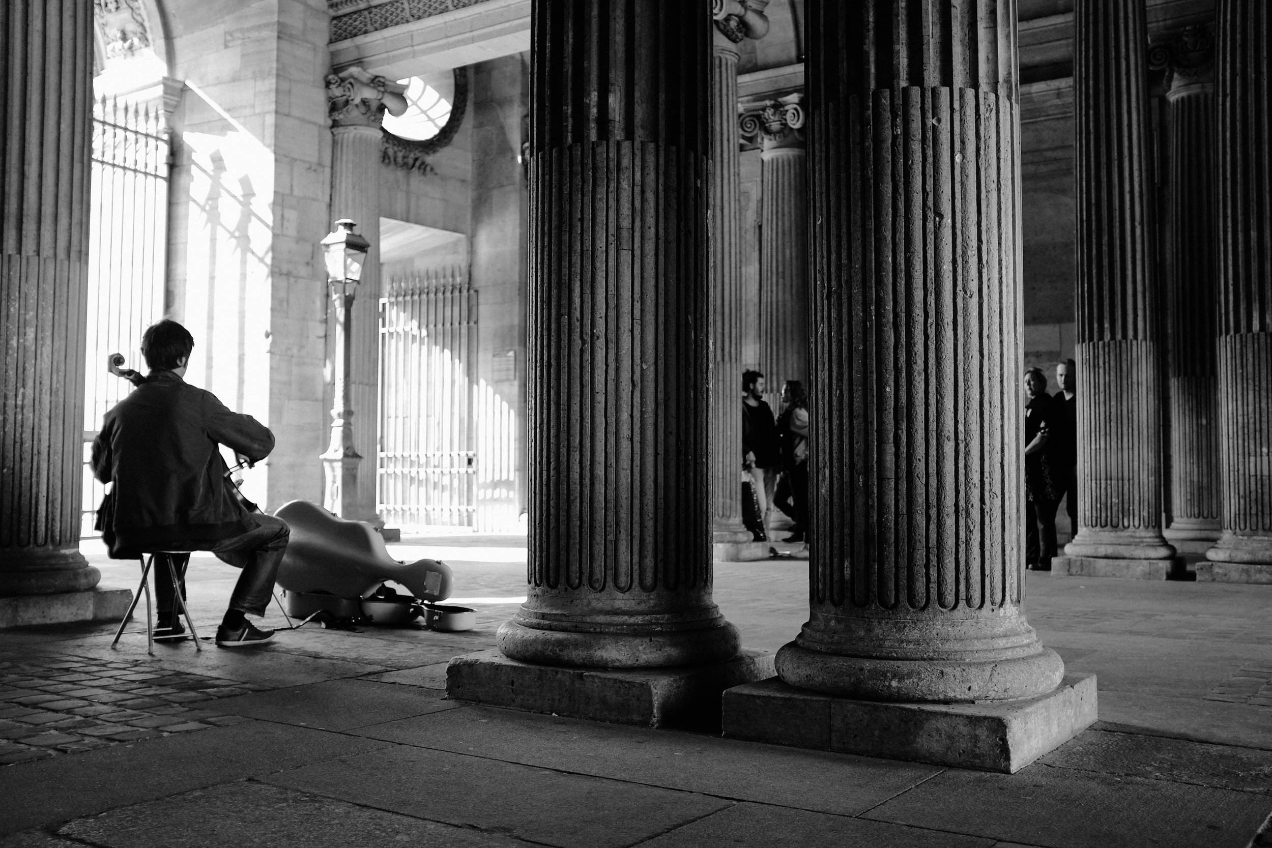 Shadows in the City of Light.  PARIS, FRANCE  —  Couples listen to a lone musician playing behind the pillars of the Louvre.