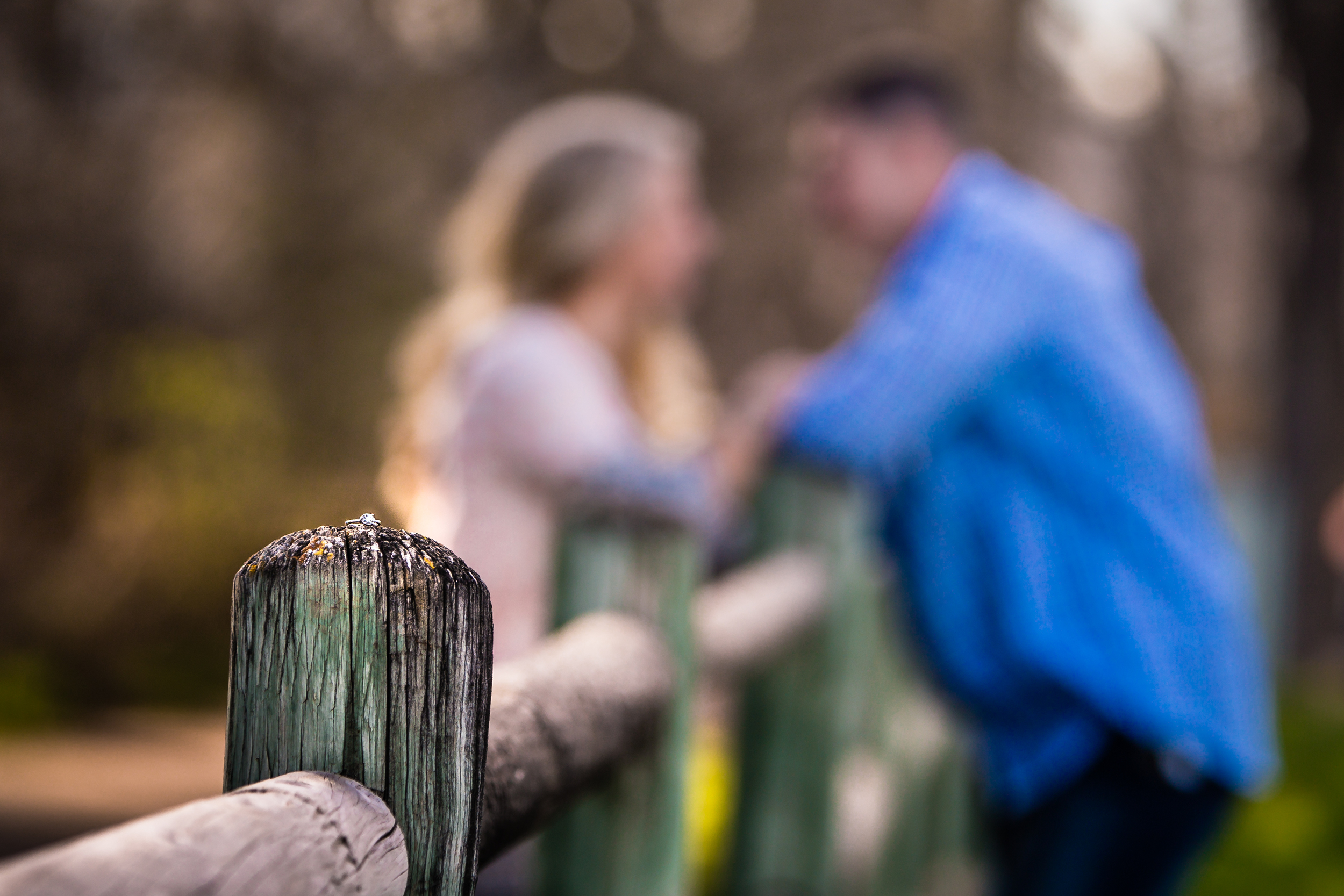 Wedding ring shot with couple in background. Engagement session in Fort Collins Colorado by JMGant Photography