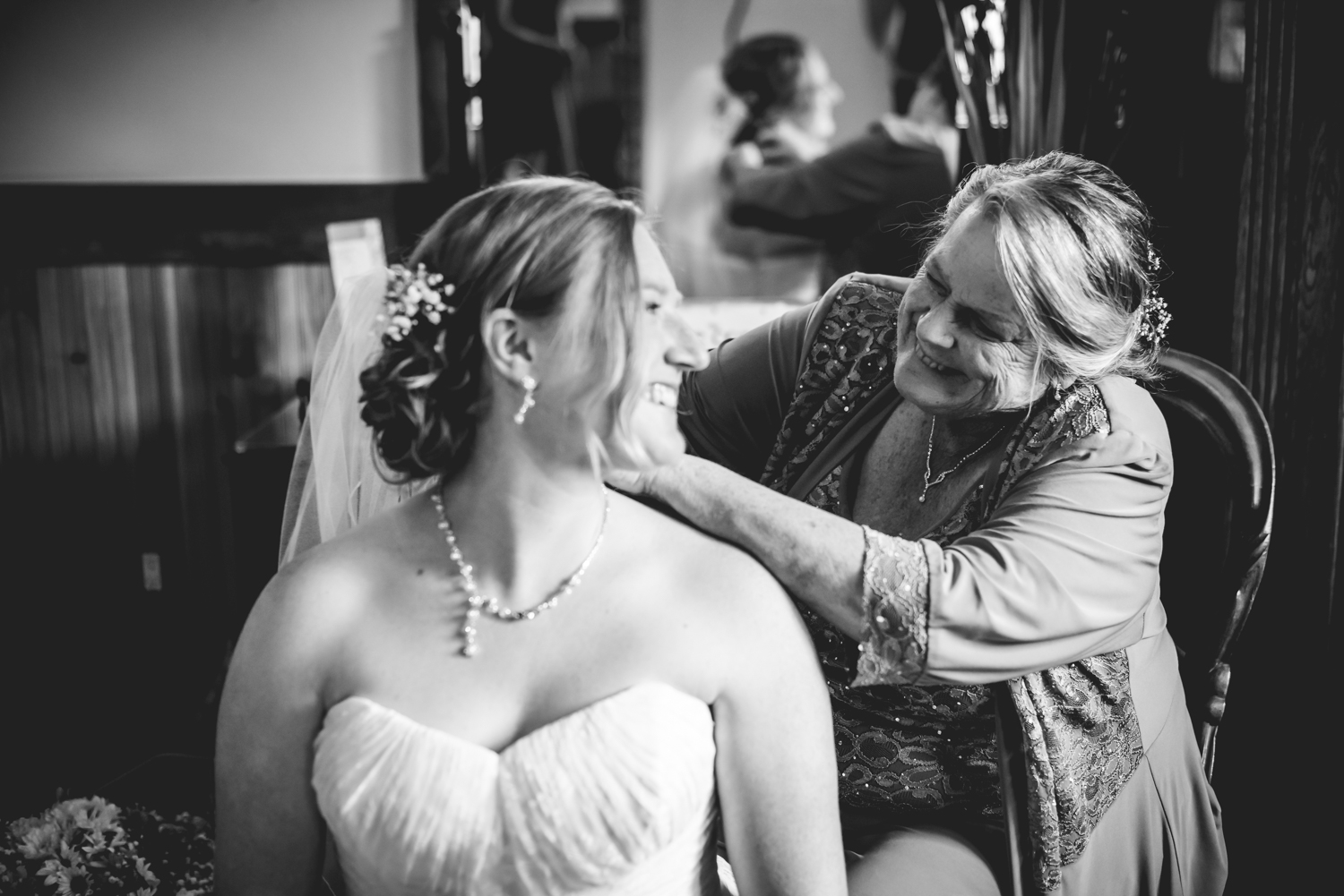 Bride's mom putting on jewelry for her Deer Creek Valley Ranch Wedding. Photographed by JMGant Photography.
