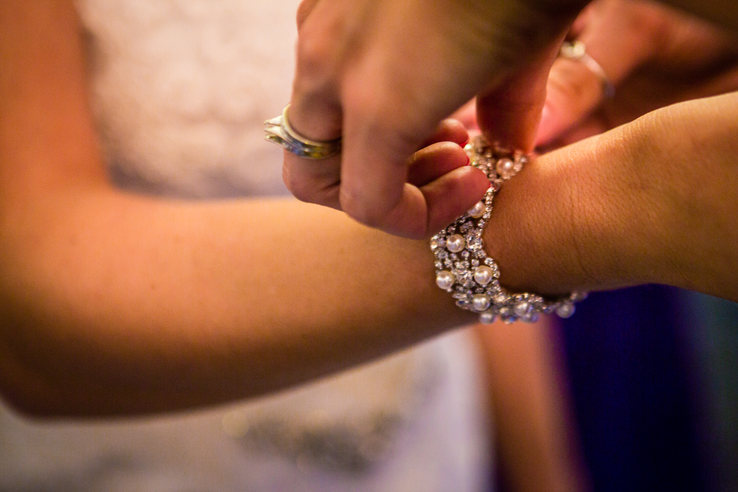 Bride putting her jewelry on. The barn at Evergreen Memorial. Photographed by JMGant Photography.