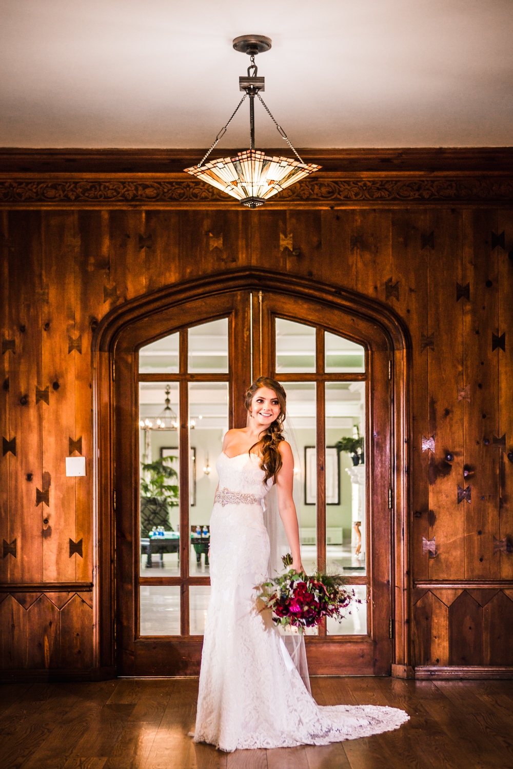 Bride in front of wood doors at Highlands Ranch Mansion. Photographed by JMGant Photography.