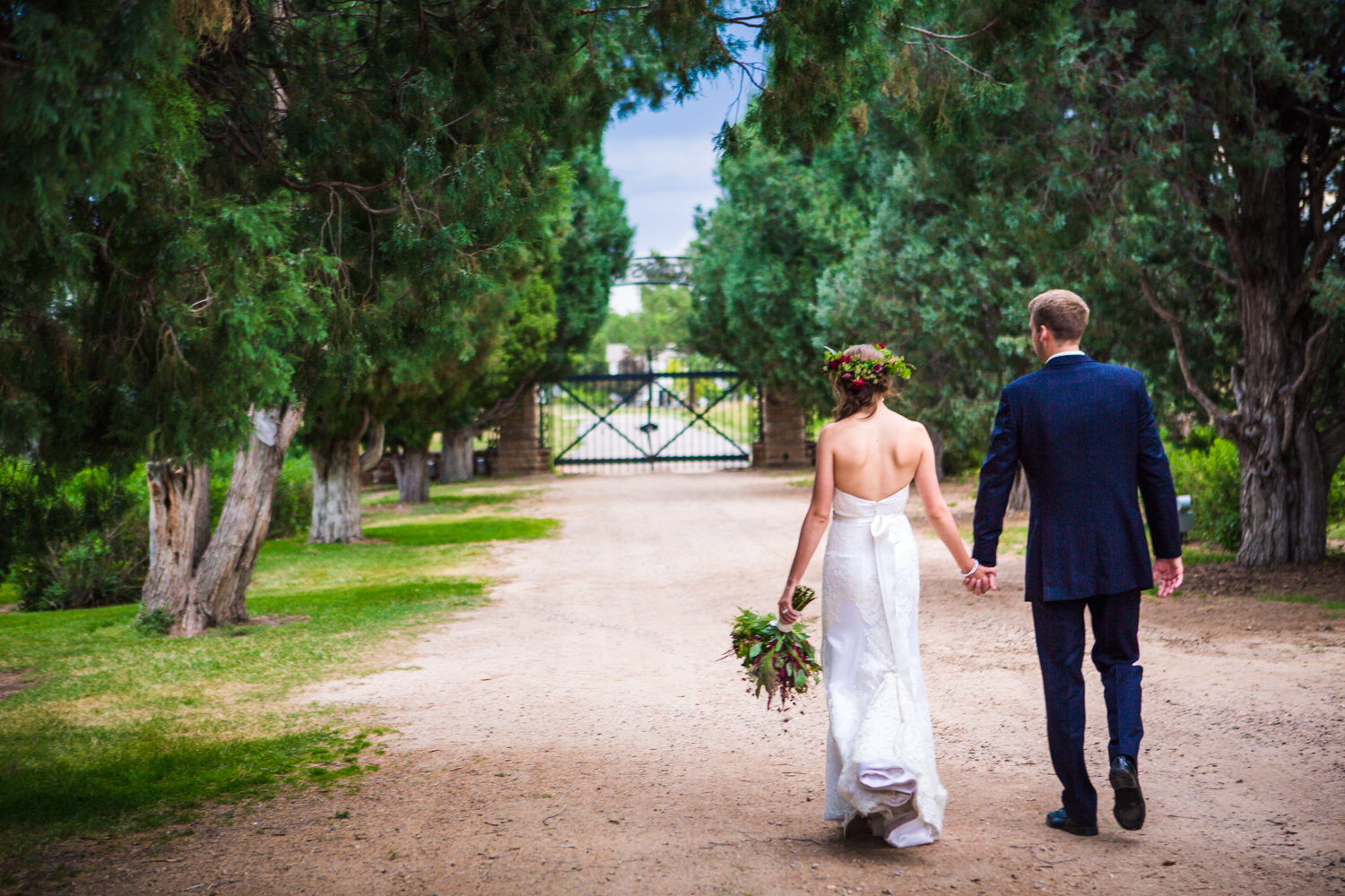 Bride and groom walking outside Highlands Ranch Mansion.    hotographed by JMGant Photography, Denver Colorado wedding photographer.