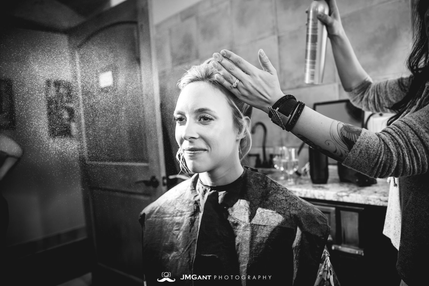 bride getting her hair done at Della Terra Mountain Chateau in Estes Park Colorado. Photographed by Jared M. Gant of JMGant Photography.
