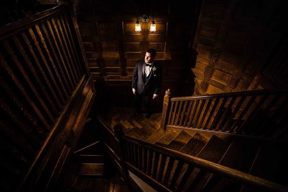 Groom on the stairs - Tapestry House winter wedding by Fort Collins wedding photographer, JMGant Photography