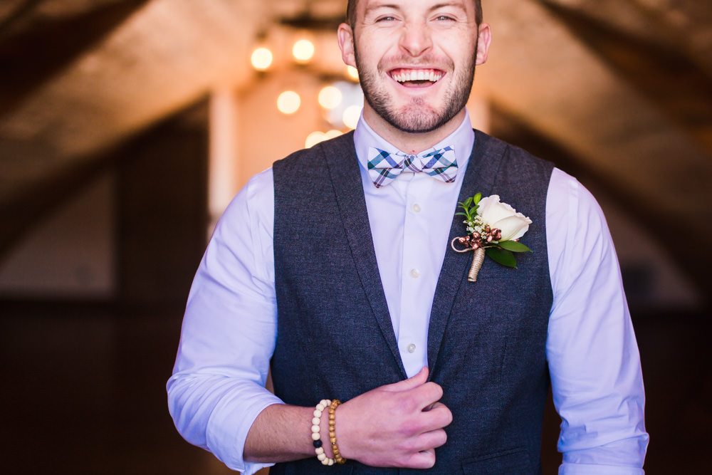 Groom wearing gray best and blue blowtie at Deer Creek Valley Ranch Wedding photographed by JMGant Photography