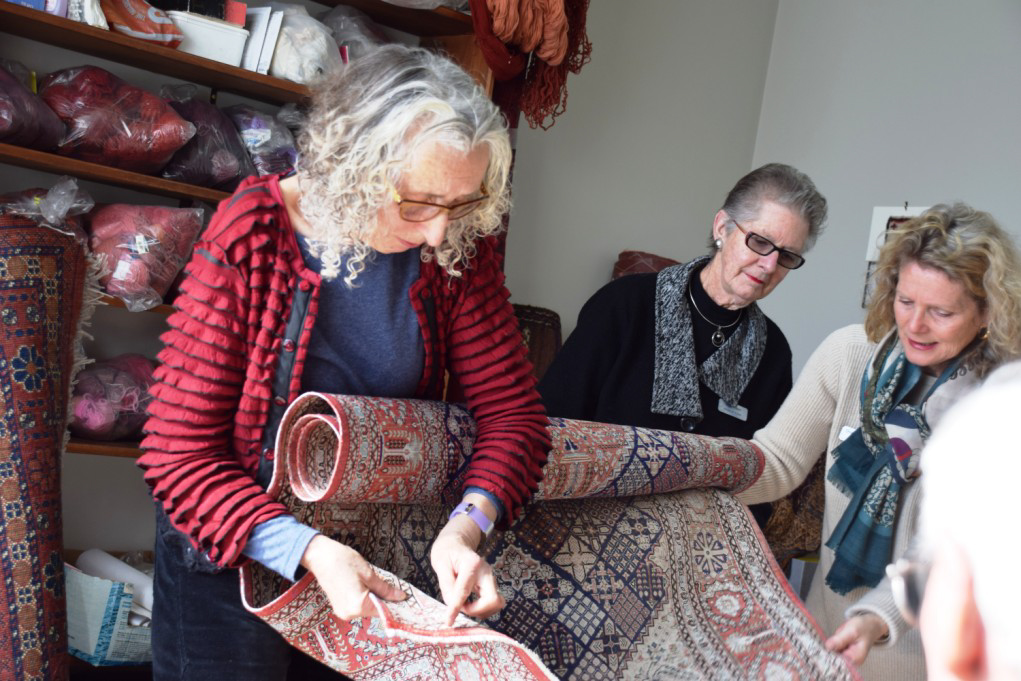 Anna Williams demonstrates rug repairs to the visiting Friends of Te Papa group. Beside her are Friends committee members Ann Hodson (left) and Sheryl Shackleton