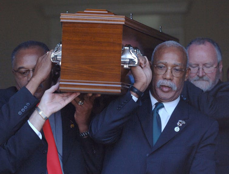 Tommie Smith (left) and John Carlos help carry of coffin of fellow 1968 medal winner Peter Norman in Melbourne, 2008