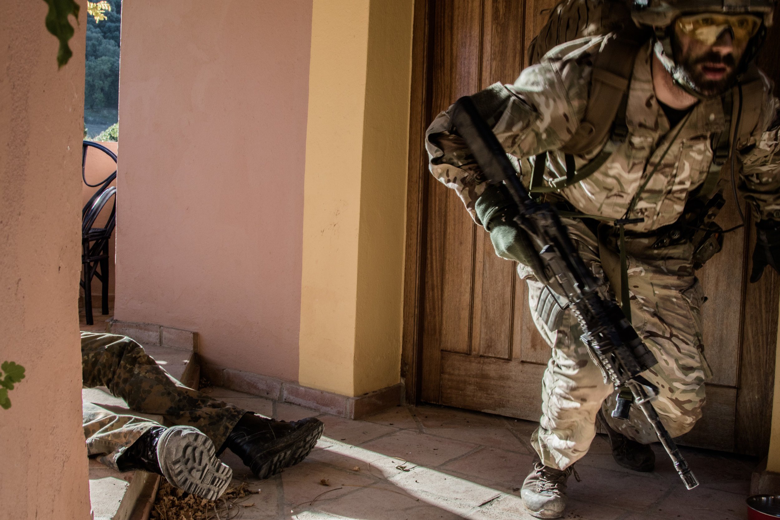 a rebel troop lies on the floor as the government soldier flees from the scene.