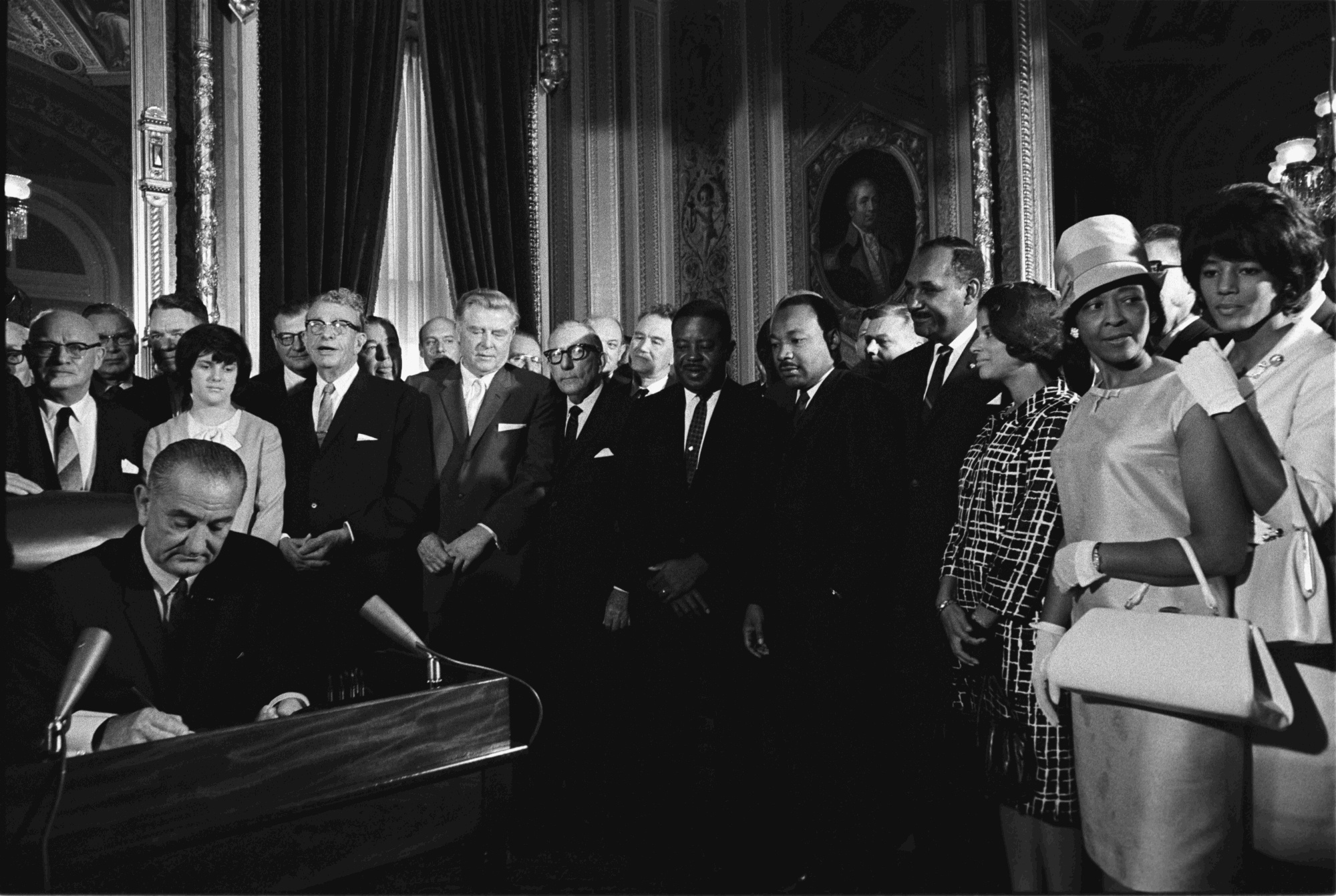 President Lyndon B. Johnson signs the Voting Rights Act of 1965 while Martin Luther King and others look on.   LBJ Library photo by Yoichi Okamoto.