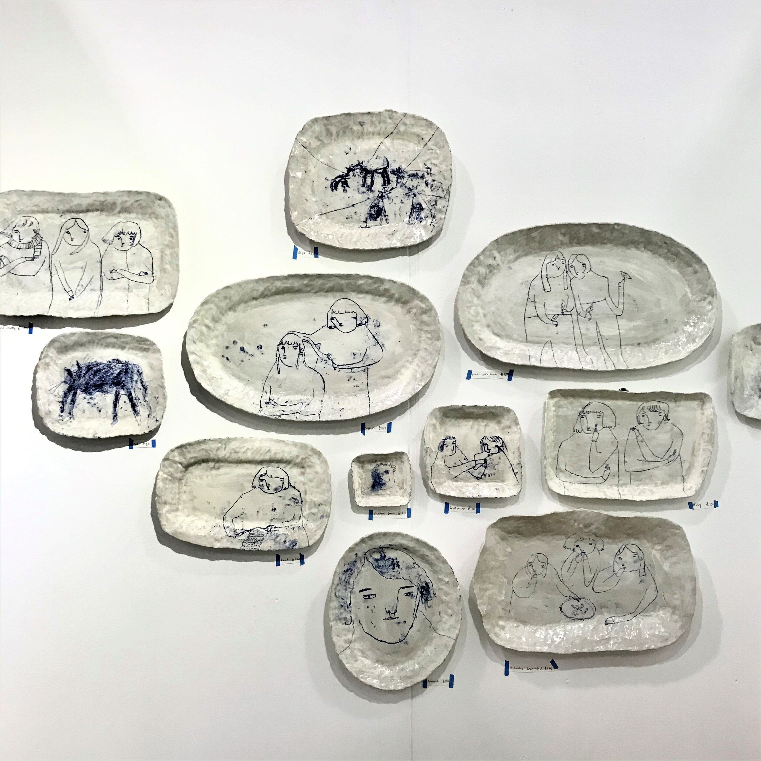Becca Brown  - The collection of story plates are created using the mono printing technique using oxide inks. These charming illustrations are conjured by strange stories and sayings. Becca builds a narrative on the surface of decorative hand built ceramics exposing brush strokes + fingerprints + making marks to accentuate the relationship between vessel and subject. www.beccabrown.co.uk