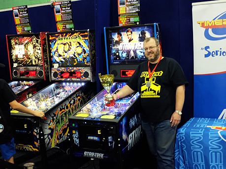 Rob adding yet another trophy to the collection.  Photo by the Australian Pinball League.