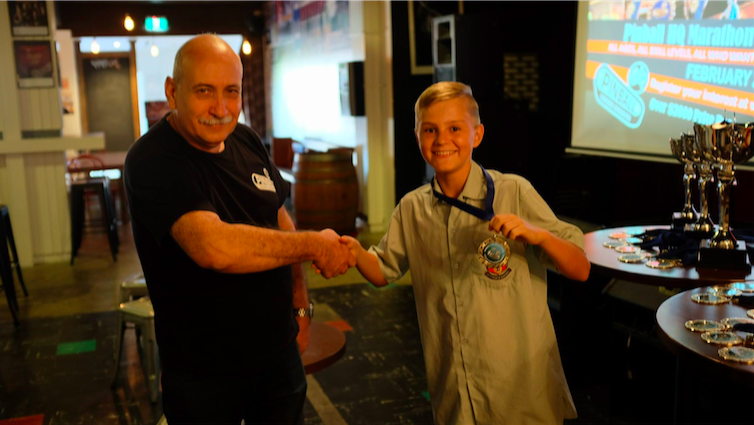 Norbert Snicer awarding the first Endurance Medal to Jett Reid, the first under 15 year old to play all 16 qualifying machines. Photo from the Pinball HQ Facebook page.