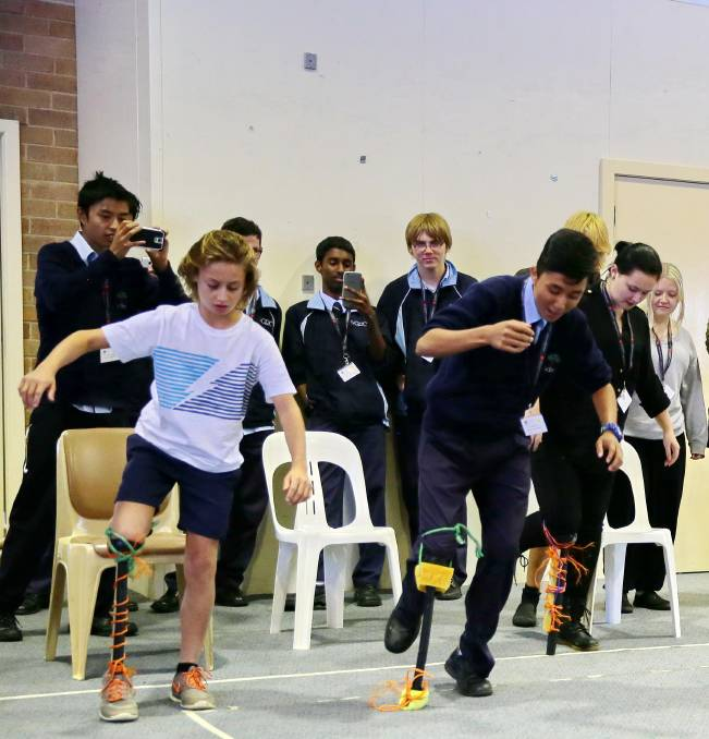 ENGINEERING: Luke Ellis from Hawker Area School (left) tests out the work of fellow who students who had to build a functioning bionic leg out of basic materials.