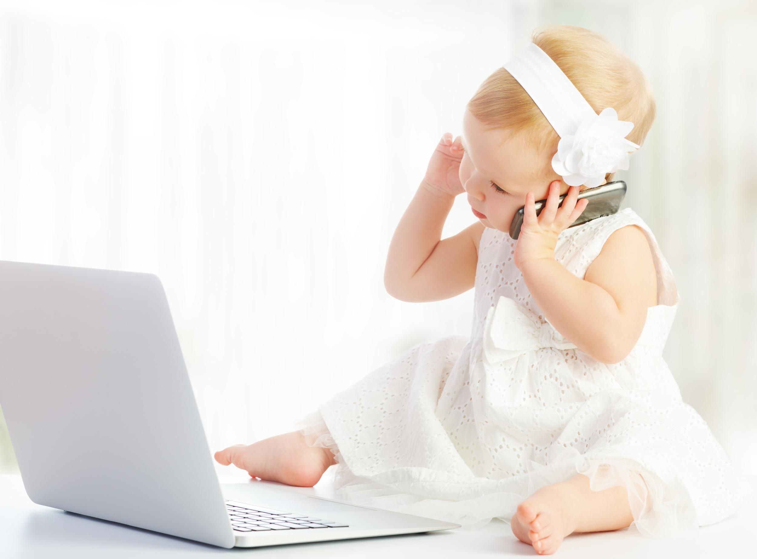 bambina con computer e smartphone