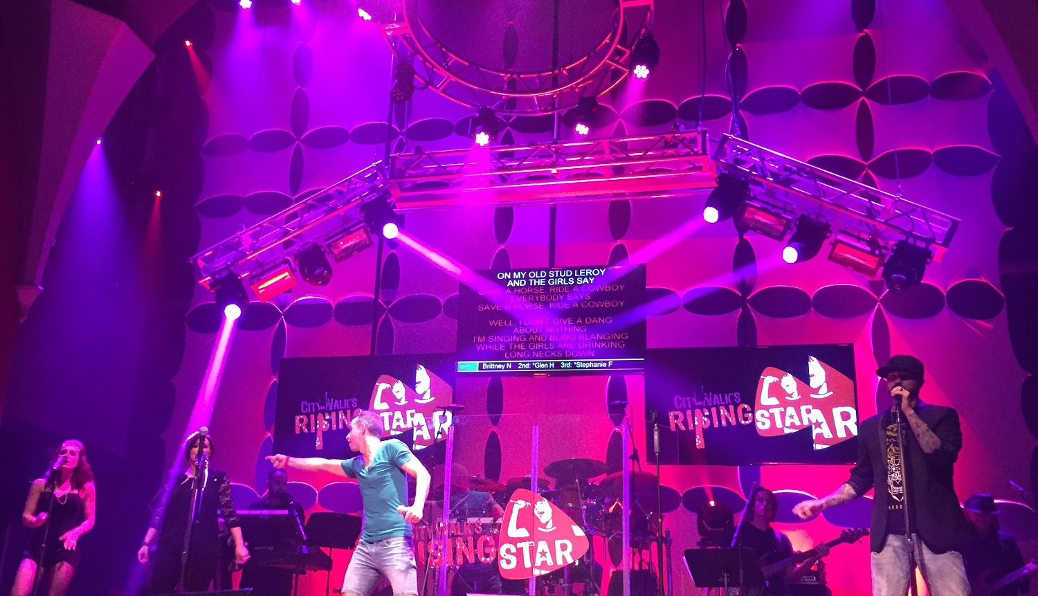A band with back-up singers accompany a performer on CityWalk's Rising Star stage.