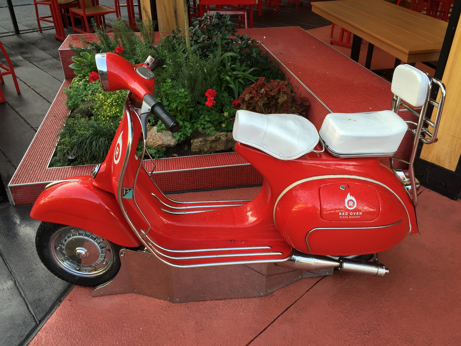 The scooter parked outside of Red Oven Pizza Bakery.