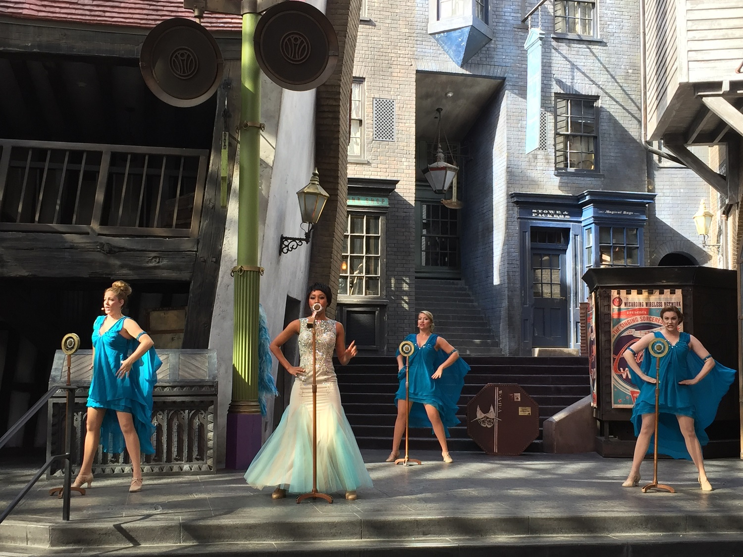 Celestina Warbeck and the Banshees perform jazzy Wizarding World themed songs on an outdoor stage in Diagon Alley.