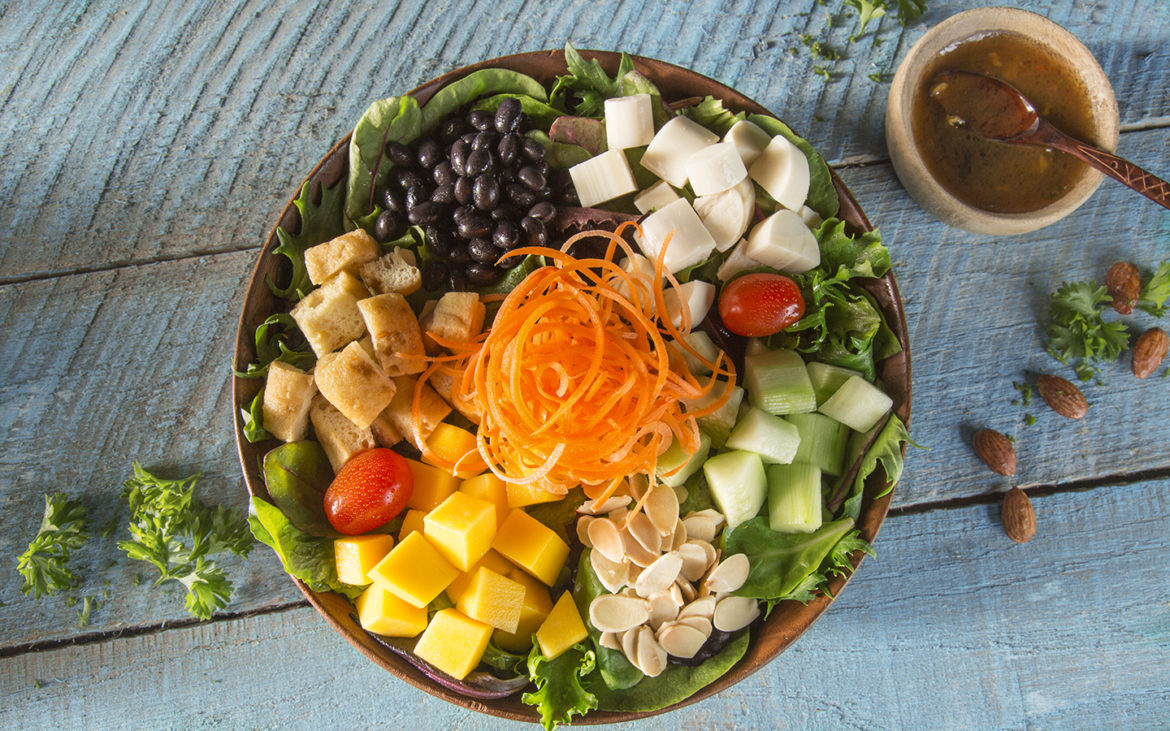 Tropical Baby Greens with Shaved Carrots, Hearts of Palm, Diced Mango, Grape Tomatoes, Cucumbers, Tofu, Black Beans, Toasted Almonds and Soy Garlic Vinaigrette.Image credit: Universal Orlando Resort.