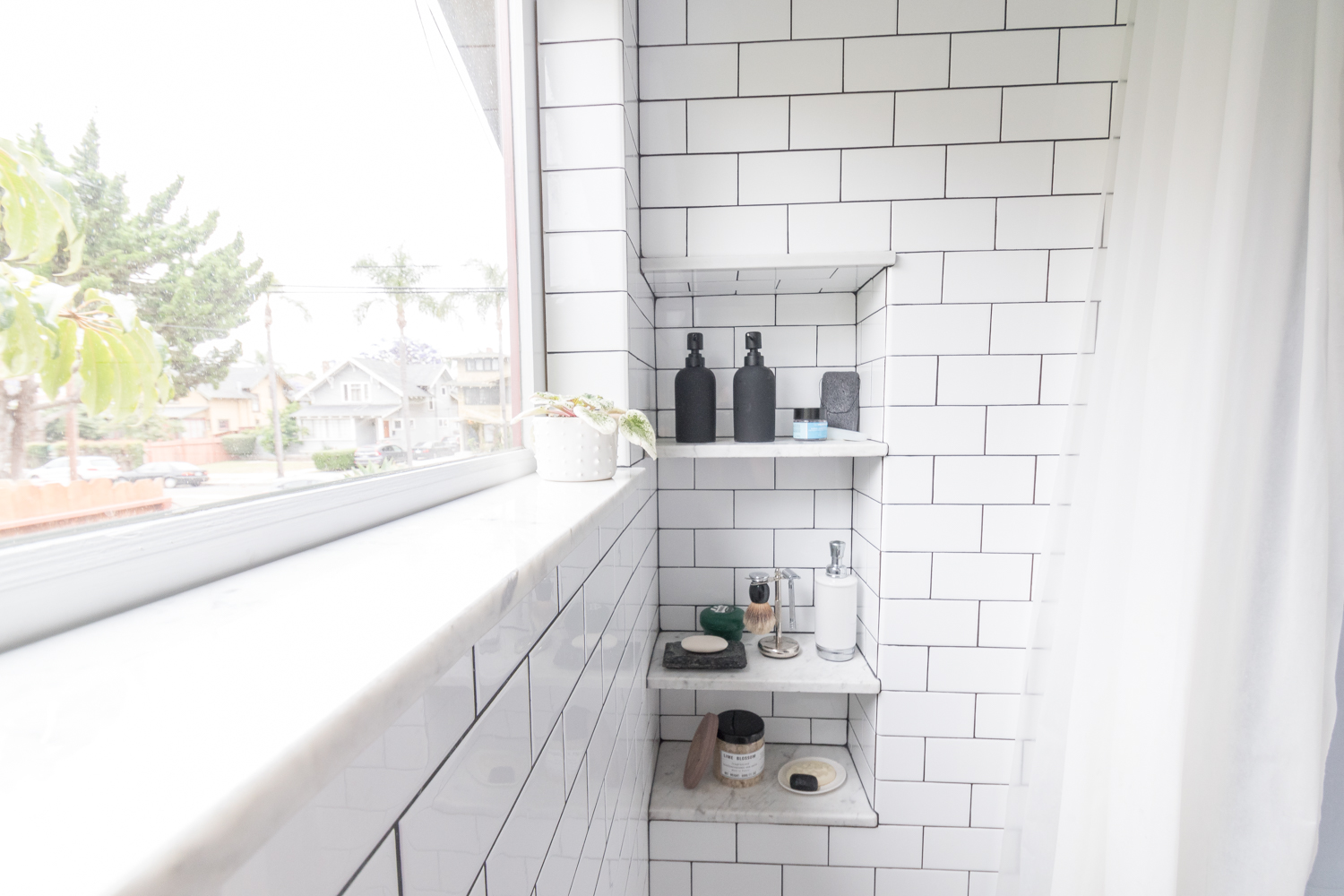 Marble sill and shelves in shower subway tile