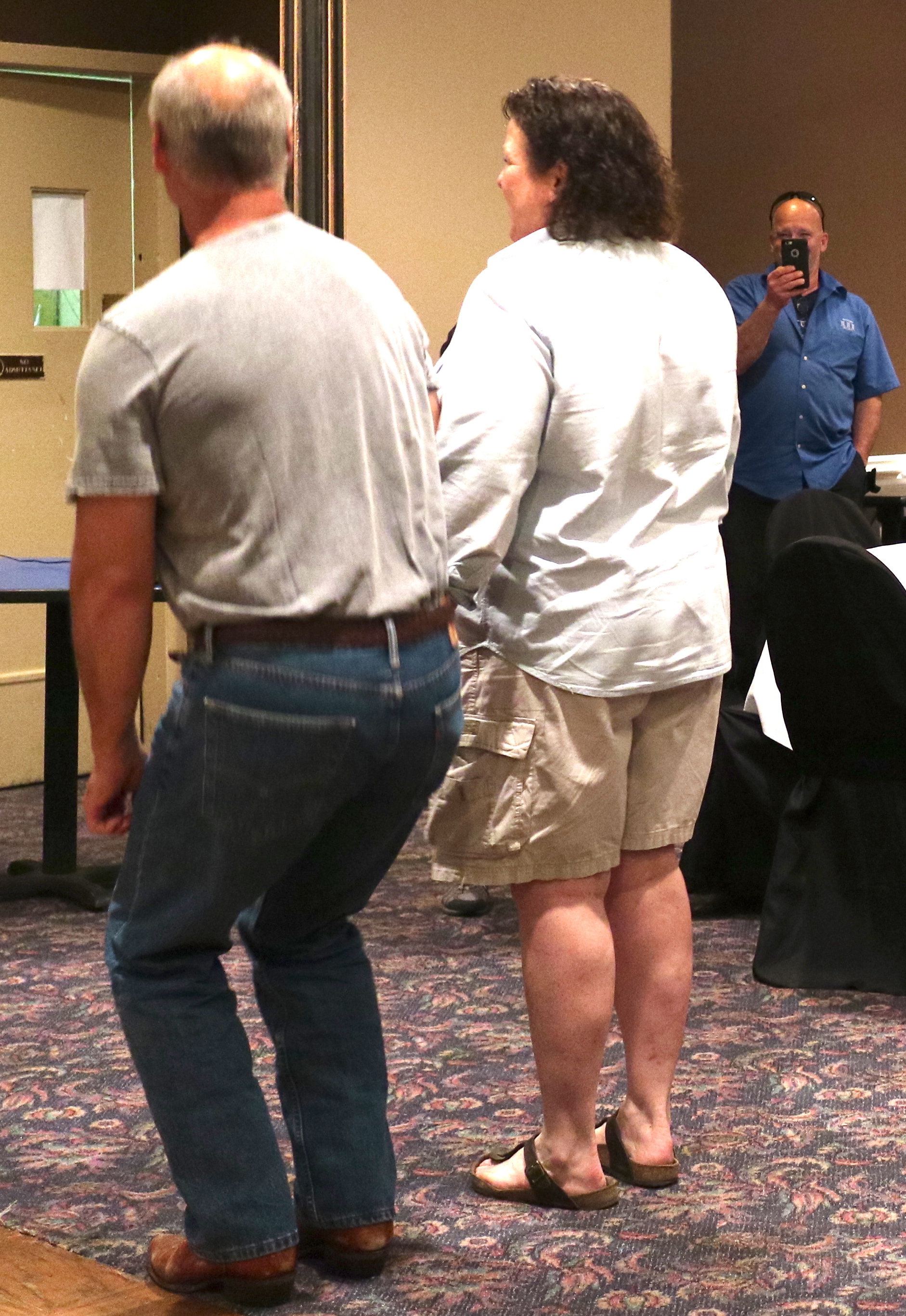Bill Long , portraying a competition obedience dog, goes into an automatic sit at halt as  Carmi Swift  portrays a successful exhibitor. Kevin Sartain  captures it on video.