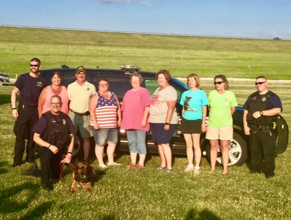 Club members  Nancy  and  Mike Kennedy, Amy Edwards, Chris Kimerer, Debbie McHenry, Sally Hamm  and  Lynette Stone  posed for a photo with O fficer Nelson, Officer Ba ker with  Stryker  and  Officer Hubbell.