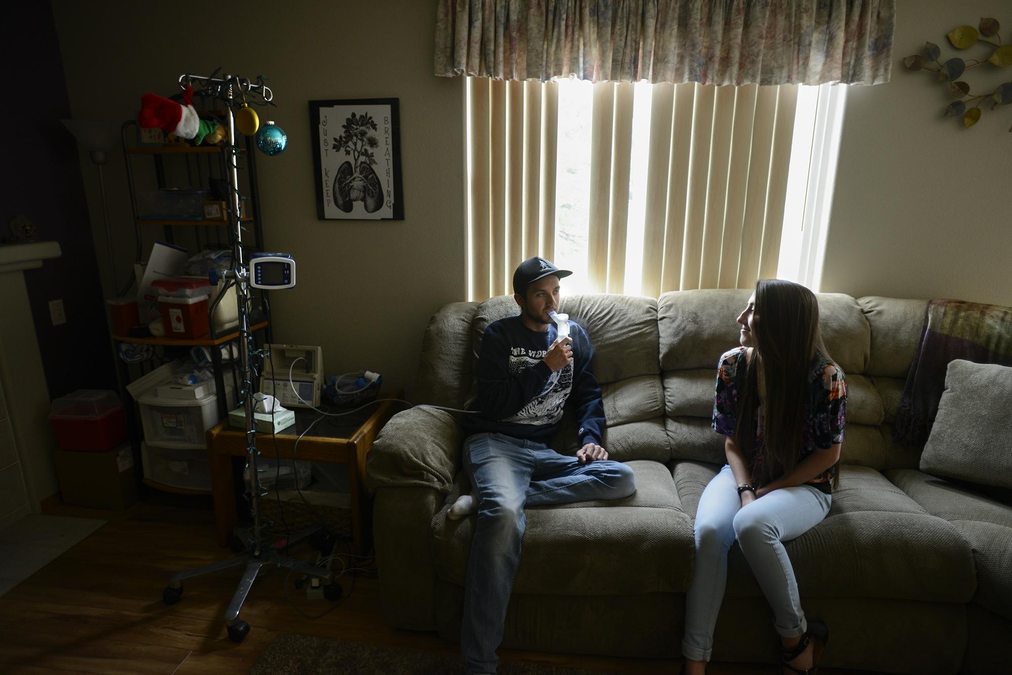 Matthew Pozsgai, left, breathes in hypertonic saline to help with his cystic fibrosis, while his sister, McKenna Pozsgai, talks to him at their Vancouver home, Tuesday July 5, 2016. After Matthew, 21, was diagnosed with cystic fibrosis, McKenna, 16, was selected by the Oregon chapter of the CF Foundation to be the voice for the 650 people in Oregon with the disease. She recently spoke with lawmakers in Washington DC about improving research and funding for cystic fibrosis. (Ariane Kunze/The Columbian)