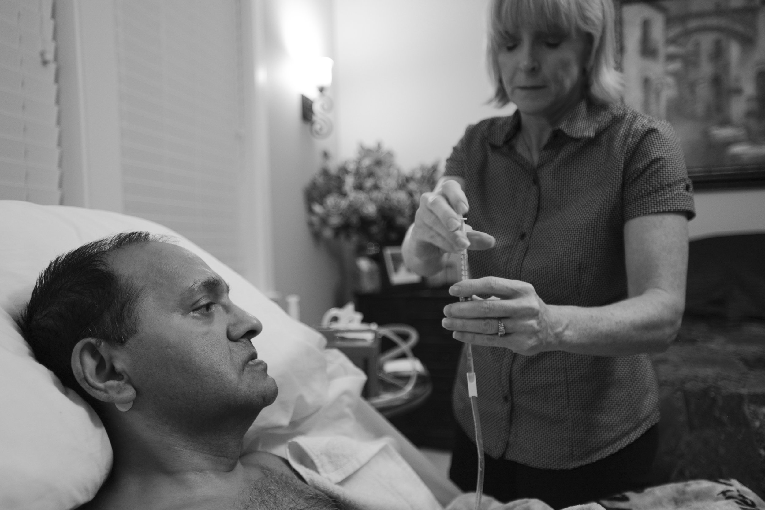 Akhil Jhaveri receives his evening medication through a feeding tube, from his wife, Laura Jhaveri August 21, 2015. Akhil was diagnosed with ALS, or Lou Gehrig's disease, in July 2011, and while he lost the ability to move his limbs and now has a feeding tube, he is trying to embrace the time he has left with his loved ones. (Ariane Kunze/The Columbian)