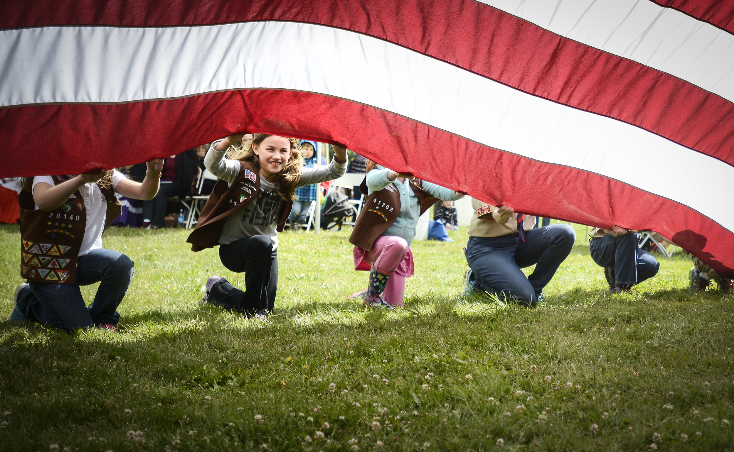 Mikaela Fisher, a member of Brownie Girl Scout Troop #45722, helps hold a flag at Fort Vancouver during the Flag Day celebration, Tuesday June 14, 2016. (Ariane Kunze/The Columbian)