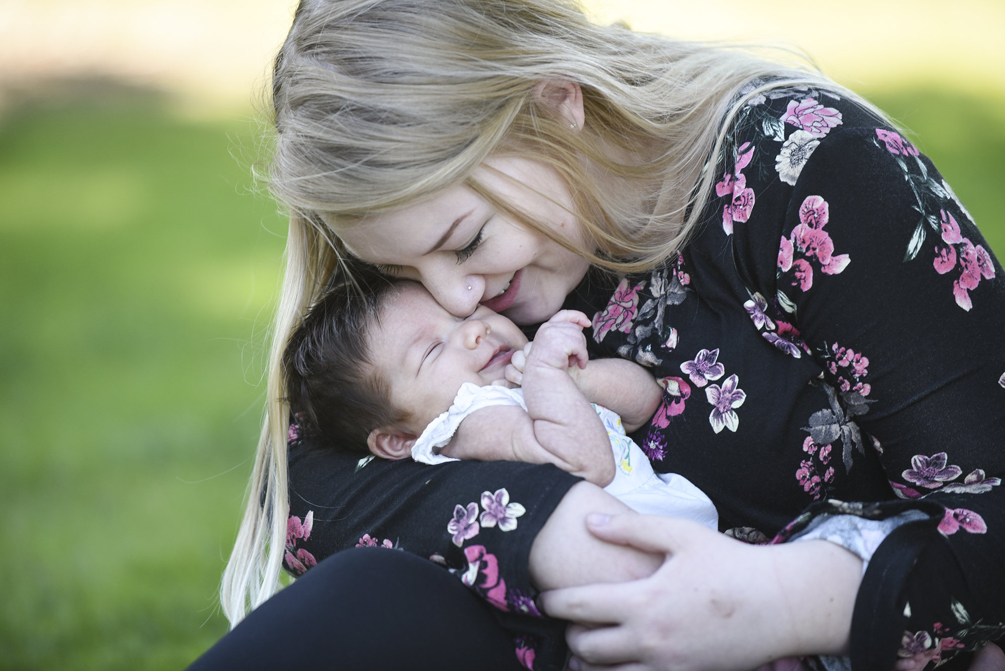 Zoe Davisson, 18, snuggles with her daughter, 7-week-old Rae Davisson at H.B. Fuller Company Park in Vancouver, Thursday September 28, 2017, during a visit with public health nurse, Joan Riemer. PeaceHealth is providing about $900,000 over three years to fund the public health program that sends nurses to the homes of new mothers. (Ariane Kunze/The Columbian)
