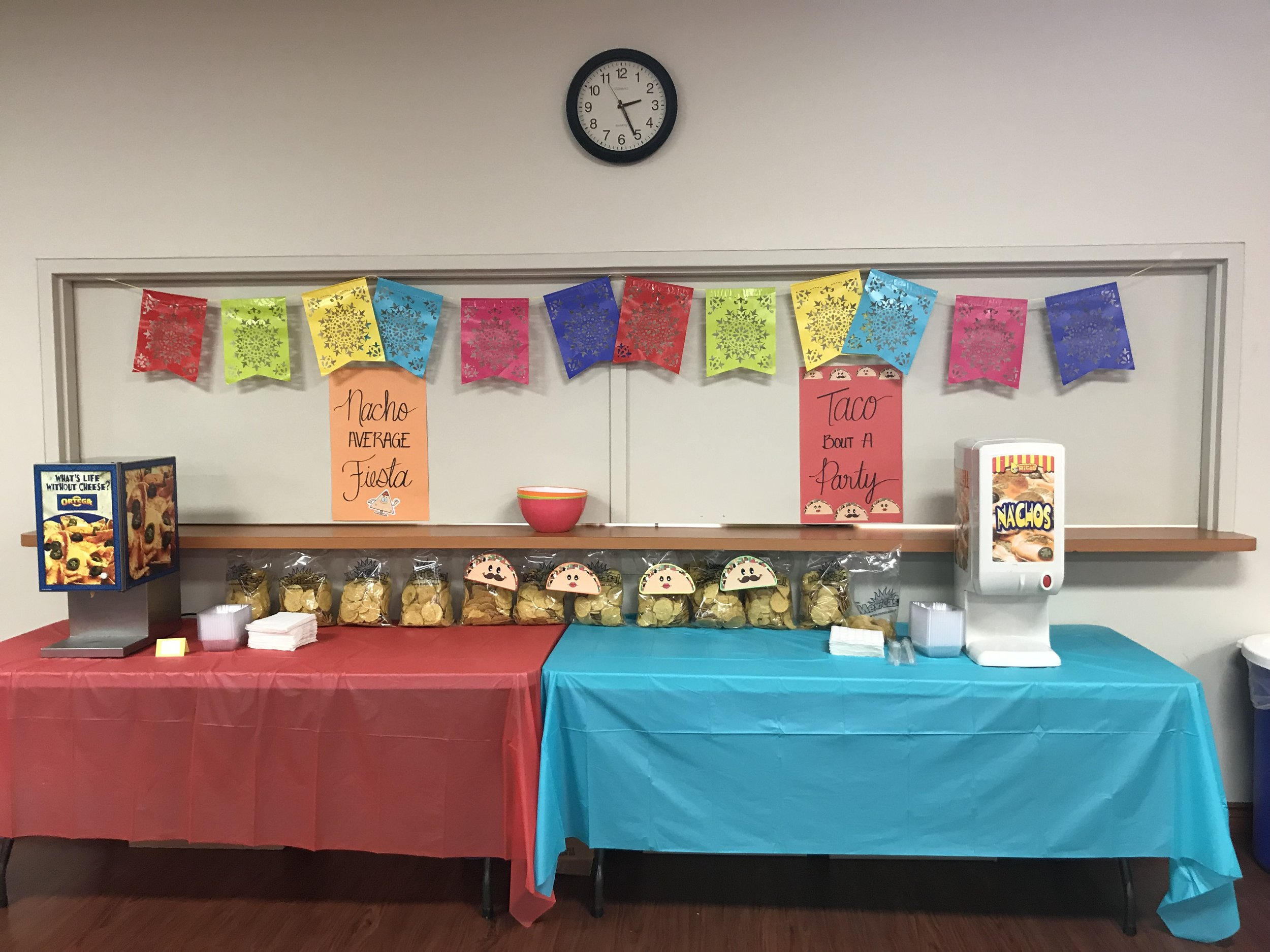 Our nacho and taco bar station. Fiesta banner from Party City, Handmade posters, free printable taco banner, Nachos and cheese from PK Snacks.