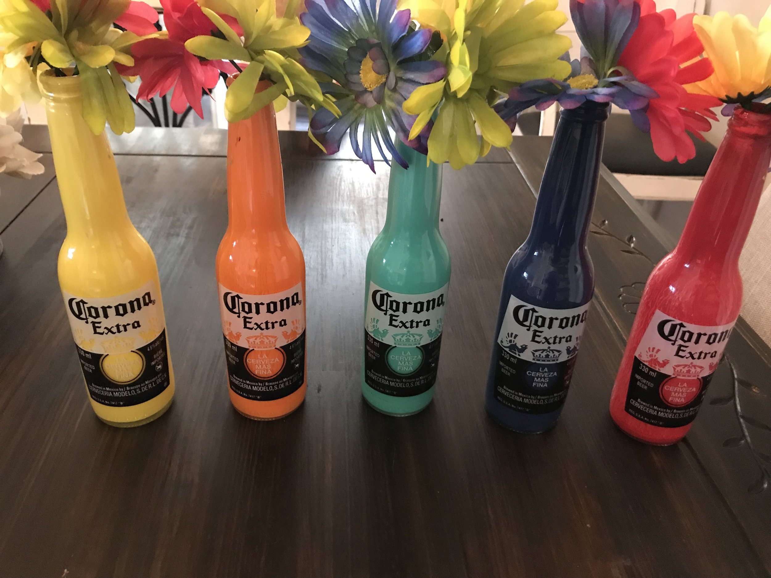 I poured acrylic paint into the bottles and rolled them around until coated with the paint. Easy peasy table decor that's perfect for a fiesta theme!