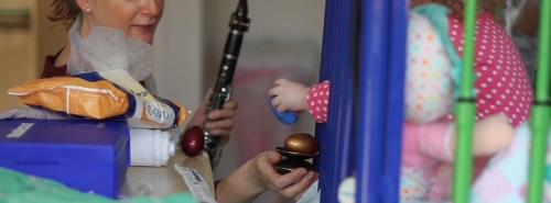 Ros responds to a child's musical lead from her cot