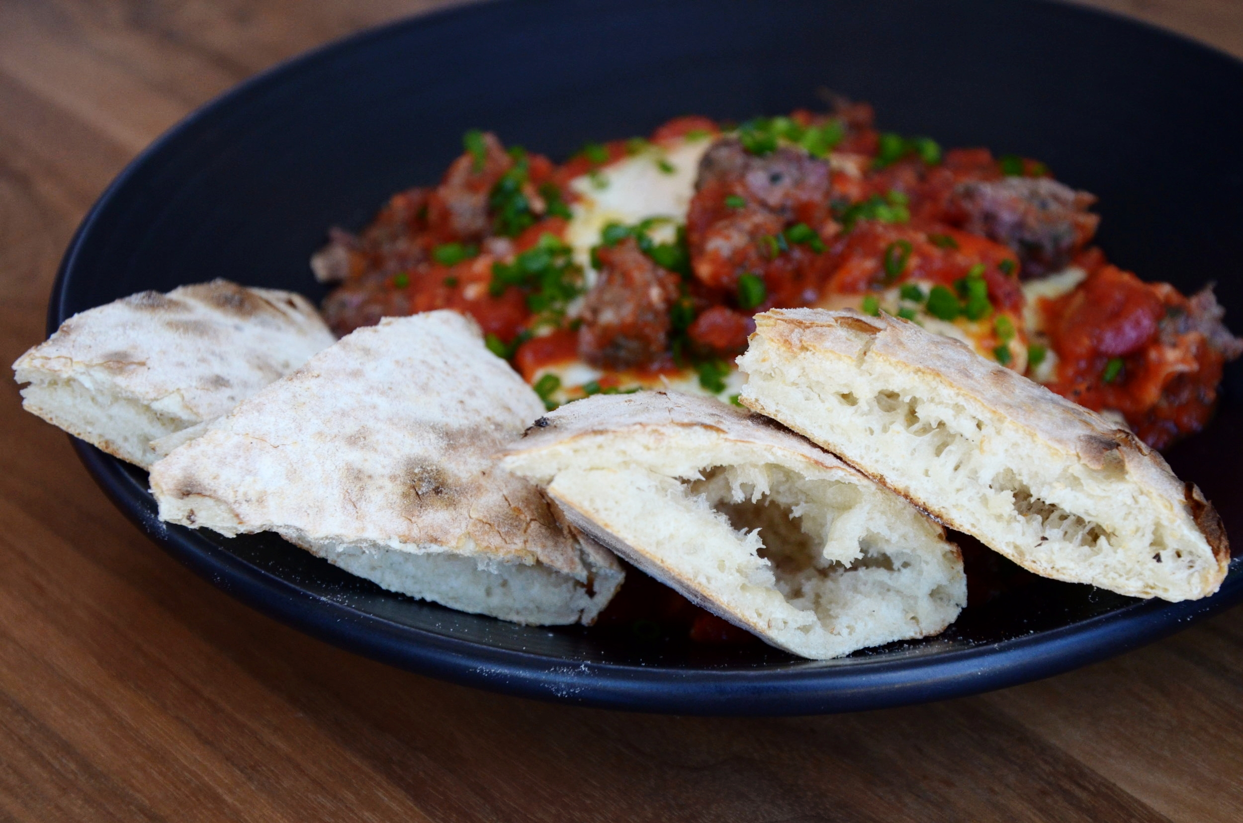 Eggs in Purgatory - lamb sausage, spicy san marzano tomatoes, rosemary polenta and house-made pita bread.