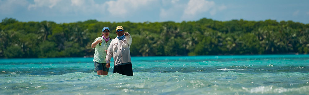 Belize fly fishing guide with angler looking for bonefish, permit, and tarpon at Turneffe Flats.