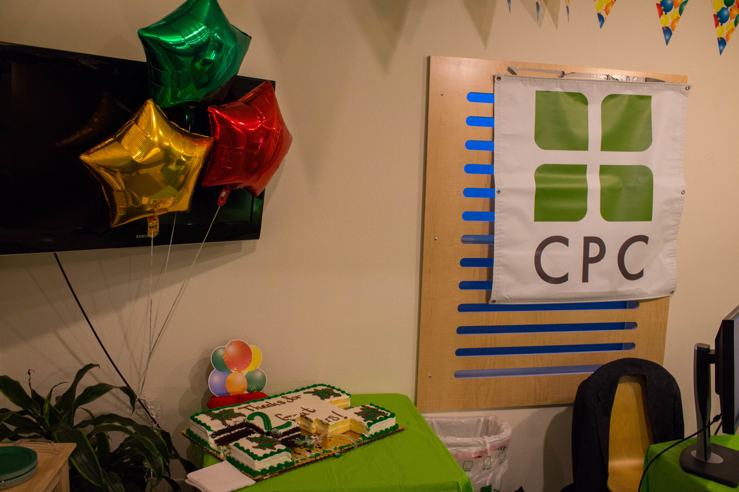 Balloons in front of TV, Cake, and CPC Banner