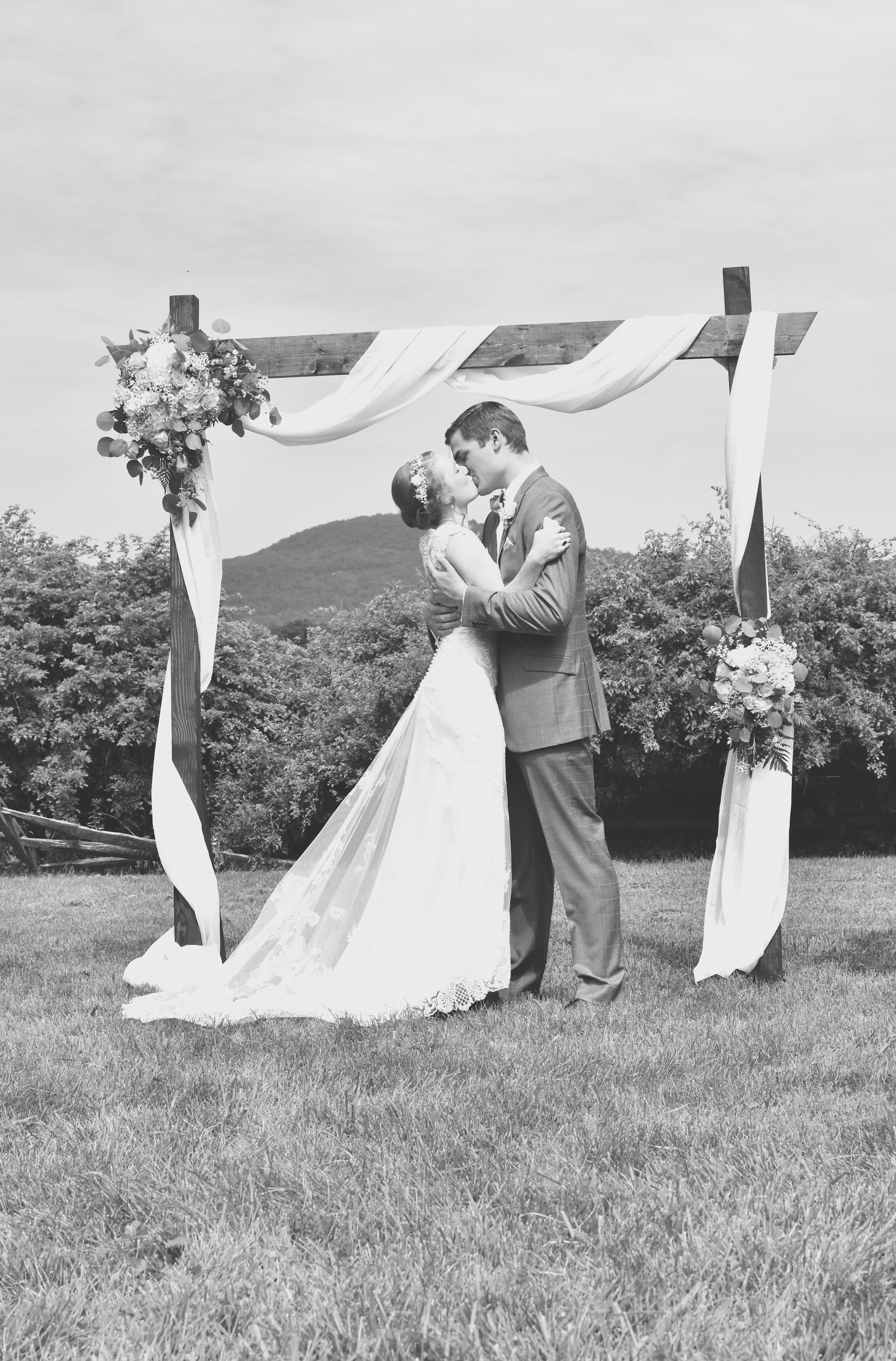you Atlanta wedding photographer kissing her husband in black and white at their wedding ceremony