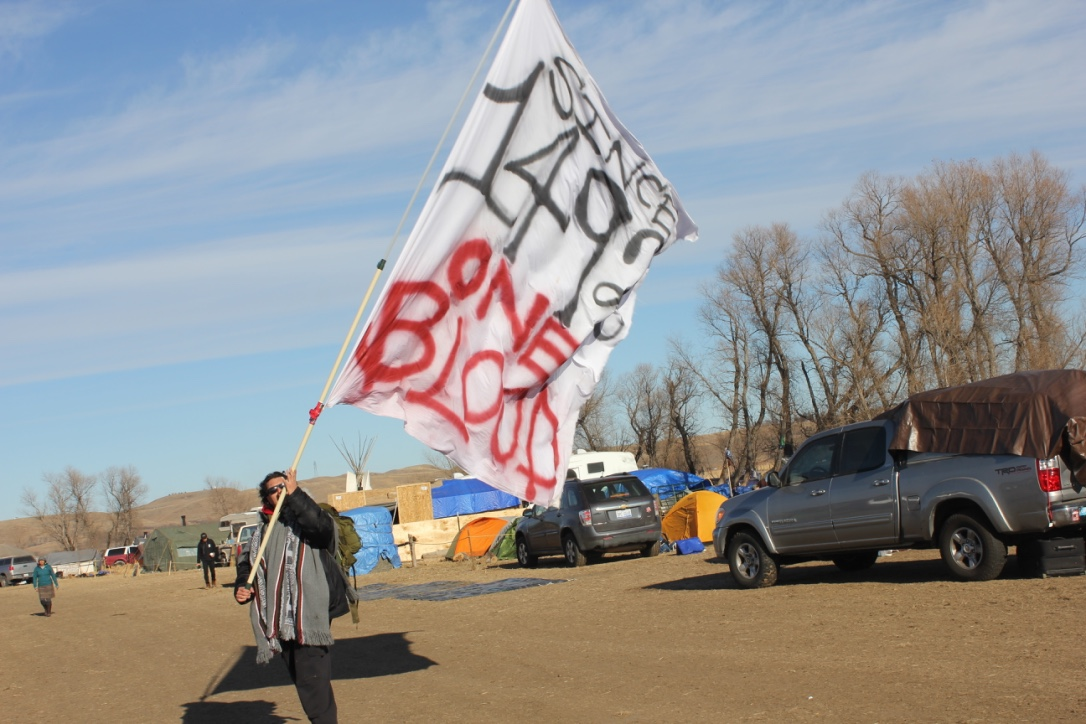 A water protector waves an impressive homemade flag, which expresses native unity against the corrosive forces of colonialism.