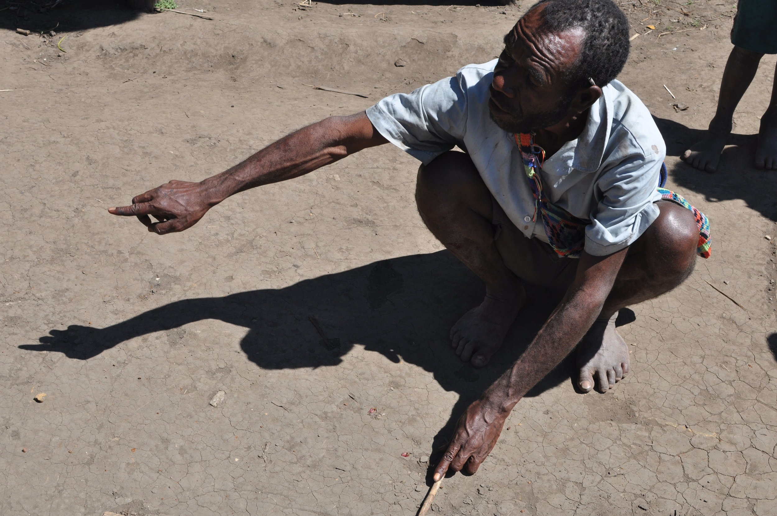 A man explains a timeline of Yupno history, recently scratched into the dirt. Gua, 2009.