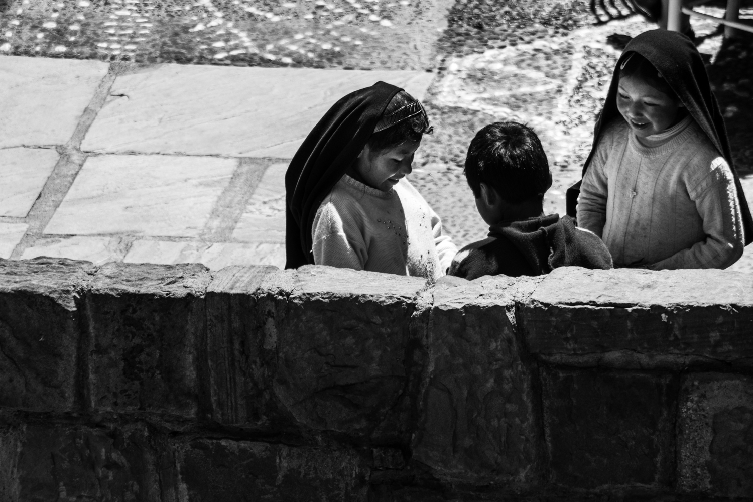 3 children on the main square in Taquile island, happily sharing the money raised selling handicrafts to the tourist.